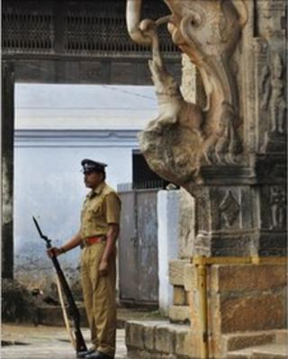 A policeman stands guard at the main entrance of the 16th-century Sree Padmanabhaswamy Temple in Trivandrum, India, Wednesday, July 6, 2011.