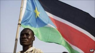 A man holds the flag of South Sudan in Juba (8 July 2011)