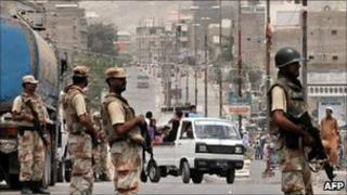 Pakistani paramilitary soldiers stand guard as residents are driven out of Karachi, 9 July 2011