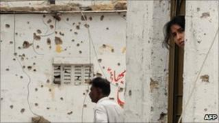 A woman peers from a doorway near a bullet-riddled wall in violence-hit Karachi, Pakistan, 9 July 2011
