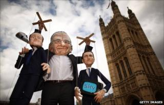 Puppets representing UK Prime Minister David Cameron (L) and Culture Secretary Jeremy Hunt (R) are held aloft by Rupert Murdoch in London (7 July 2011)