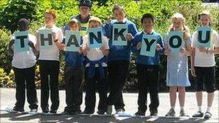 "Schoolchildren with ""thank you"" message"