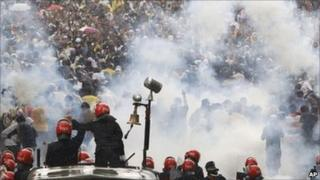 Malaysian riot police officers fire tear gas at activists from Coalition for Clean and Fair Elections (Bersih) during a rally in Kuala Lumpur, Malaysia, Saturday 9 July