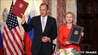 Russian Foreign Minister Sergey Lavrov and US Secretary of State Hillary Clinton hold up the agreement on adoption in Washington, DC