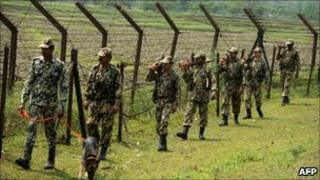 Indian Border Security Force soldiers patrol along the India-Bangladesh border at Fulbari on 17 April 2011