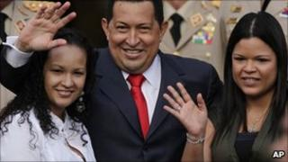 Venezuela's President Hugo Chavez, waves flanked by his daughters Rosa Virginia (R) and Gabriela, after he announced he would return to Cuba Saturday to begin a new phase of cancer treatment that would include chemotherapy