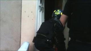 A police officer breaks down a door