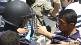 Protesters clash with riot police during a demonstration in Amman, 15 July, 2011