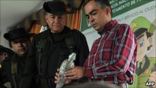 Colombia's police chief General Oscar Naranjo (C) and Defence Minister Rodrigo Rivera (R) inspect a homemade mortar shell, part of a seizure in Arauca on 17 July 2011