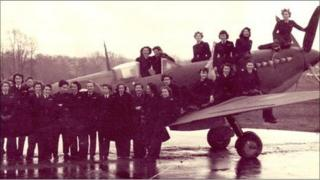 A group of women posing with a spitfire at Hamble Airfield in Southampton