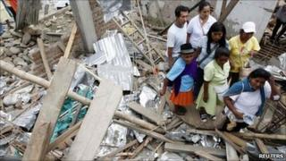 A family looks at their house that was damaged after being hit by a blast in Toribio, in Cauca province, 9 July, 2011.