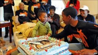 """A picture released by the Mandela Family shows South Africa""""s iconic elder statesman Nelson Mandela (2ndL), dubbed Madiba, celebrating his birthday with his family in Qunu on July 18, 2011 as baby Zama Obiri cuts the cake with Mbuso Mandela"""
