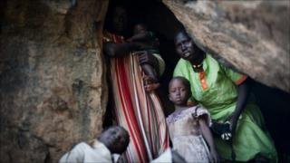 A terrified mother looks out of a cave as she takes shelter from an aircraft flying over the hills surrounding Lwere in Sudan's Nuba mountains on 1 July as hundreds of families have fled their villages in South Kordofan following recent bombing by the Sudanese armed forces