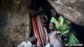 A terrified mother looks out of a cave as she takes shelter from an aircraft flying over the hills surrounding Lwere in Sudan's Nuba mountains on 1 July 1.