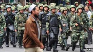 Armed Chinese soldiers march on patrol as a Uighur man crosses the street in Urumqi on July 15, 2009 in north-west China's Xinjiang province