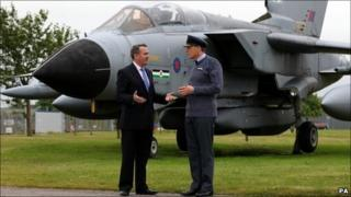 Defence Secretary Liam Fox speaks with Station Commander Group Captain Andy Hine in front of a Tornado GR4 at RAF Lossiemouth