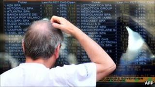 A man looks at a board outside Milan's stock exchange