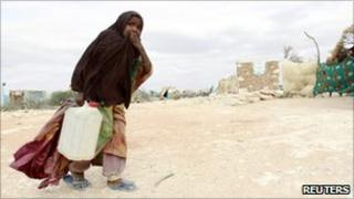 """A displaced Somali girl carries water at the Halabokhad IDP settlement in Galkayo, northwest of Somalia""""s capital Mogadishu, 20 July 2011"""