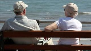 An elderly couple sitting on a bench and looking out to sea
