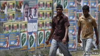 Two men walk past local government election campaign posters in Jaffna, Sri Lanka, on Friday