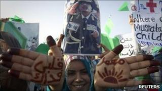 "A pro-Gaddafi demonstrator shows script on her hands reading ""I'll sacrifice my life for Muammar"" in Sirte, the hometown of Libyan leader Col Gaddafi, on 21 July."