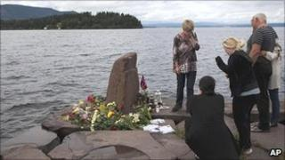 Relatives mourn a lost loved one opposite Utoeya island