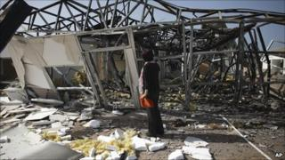 In this photo taken on a government-organized tour, a journalist inspects a building that Libyan officials say was destroyed in an air strike, near the town of Zlitan, roughly 160 kilometres (99 miles) east of Tripoli