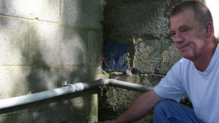 Lex XI chairman Dennis Hall, inspecting plastic piping which has had to replace the stolen copper pipes