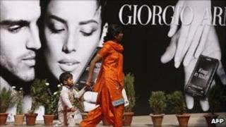 Woman and child walk past Giorgio Armani poster in India