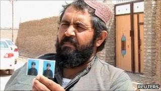 Afghan policeman Daoud holds up a photo of his murdered son, Ibrahim