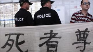 Policemen stand beside a resident who holds a banner at a railway station in Wenzhou, Zhejiang province July 27, 2011