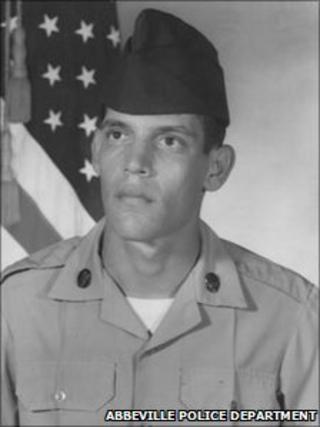 A photograph of Joseph W Schexnider sitting next to an American flag