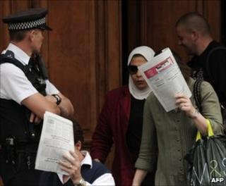 Women emerging from the Libyan embassy in London cover their faces as a British policeman looks on, 27 July