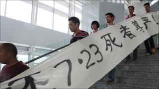 Protesters carrying a banner saying 'return dignity to the victims who died on July 23' demonstrate in the hope of learning the truth of the July 23 high-speed train collision, at a railway station in Wenzhou, in eastern China's Zhejiang province on July 27,
