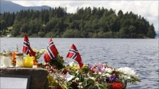 Norwegian flags and flowers on the lakeshore in front of Utoeya island to commemorate victims of the shootings there - 27 July 2011
