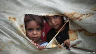 Internally displaced children peep through a tent used by their family at a camp for flood victims in Sir Darriyya, Charsadda, northwest Pakistan July 28, 2011.