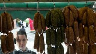 Man looking at sausages in a butcher shop window