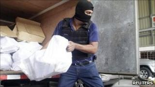 A police officer unloads bags of confiscated drugs at a police station in Panama City - some 639 packages of heroin and 468 packages of cocaine were confiscated during two different operations in the province of Colon and Panama City