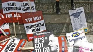 Discarded placards are left in the street as a child rests on a wall during a nationwide day of strikes in central London, Thursday, June 30, 2011.