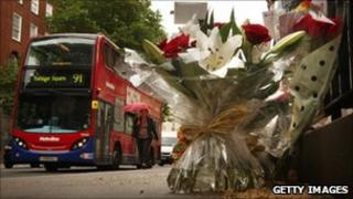 A bus passes floral tributes placed next to a memorial remembering the victims of the London bus bombing