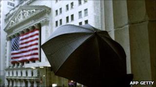 Person holding umbrella under US flag