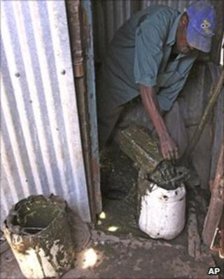 A worker tries to unclog a pit latrine