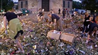 Workers clear away flowers and other items left outside Oslo's cathedral in honour of victims of the 22 July attacks - 3 August 2011