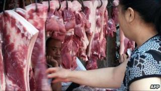 A Chinese customer selects pieces of pork at a market in Yichang, central China's Hubei province