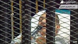 Mubarak appeared on a stretcher inside the defendants' cage