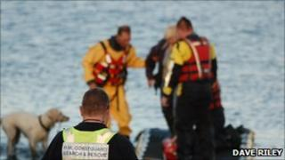 The woman being rescued by firefighters and a member of the coastguard