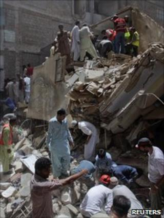 Rescuers look through the rubble of the building which collapsed in Karachi on 4 August 2011
