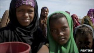 Women and children queue to receive food at a World Food Programme food distribution centre in Mogadishu, Somalia on 4 August 2011