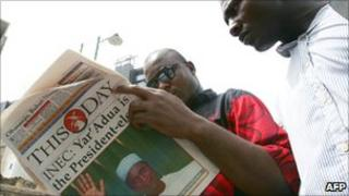 Nigerians reading a newspaper