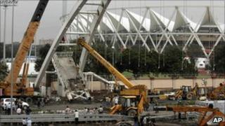 A crane lifts debris from a pedestrian bridge that collapsed outside the Jawaharlal Nehru Stadium (22 September 2010)